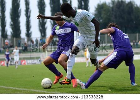 KAPOSVAR, HUNGARY - SEPTEMBER 14: Mustapha Diallo (in white 27) in action at a Hungarian Championship soccer game - Kaposvar (white) vs Ujpest (purple) on September 14, 2012 in Kaposvar, Hungary. - stock photo