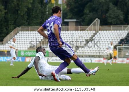 KAPOSVAR, HUNGARY - SEPTEMBER 14: Mustapha Diallo (white) in action at a Hungarian National Championship soccer game - Kaposvar (white) vs Ujpest (purple) on September 14, 2012 in Kaposvar, Hungary. - stock photo