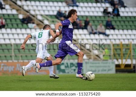 KAPOSVAR, HUNGARY - SEPTEMBER 14: Nikola Safaric (in white) in action at a Hungarian National Championship soccer game - Kaposvar (white) vs Ujpest (purple) on September 14, 2012 in Kaposvar, Hungary. - stock photo