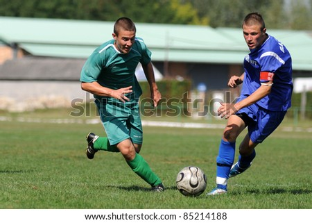 KAPOSVAR, HUNGARY - SEPTEMBER 18: Unidentified players in action at the Hungarian Championship under 17 game between Kaposvar (green) and Baja (blue) on September 18, 2011 in Kaposvar, Hungary. - stock photo