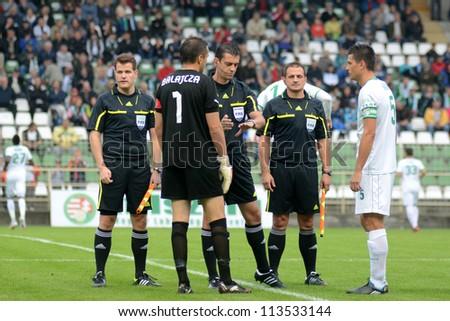 KAPOSVAR, HUNGARY - SEPTEMBER 14: Viktor Kassai (C) at a Hungarian National Championship soccer game - Kaposvar (white) vs Ujpest (purple) on September 14, 2012 in Kaposvar, Hungary. - stock photo