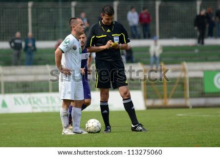 KAPOSVAR, HUNGARY - SEPTEMBER 14: Viktor Kassai (referee) in action at a Hungarian National Championship soccer game - Kaposvar (white) vs Ujpest (purple) on September 14, 2012 in Kaposvar, Hungary. - stock photo