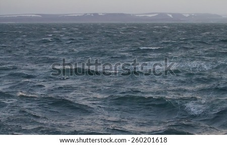 Kara sea near the island of Novaya Zemlya. High sharp waves in the Arctic sea. On the horizon of the Northern island of Novaya Zemlya - stock photo
