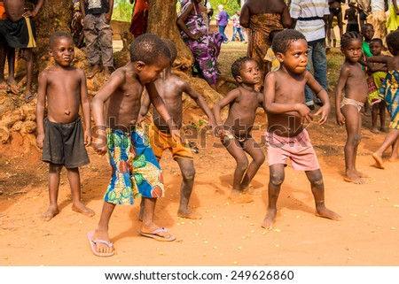 KARA, TOGO - MAR 9, 2013: Unidentified Togolese children dance and play during a local dance show. People in Togo suffer of poverty due to the unstable econimic situation - stock photo