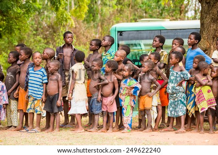 KARA, TOGO - MAR 9, 2013: Unidentified Togolese children watch the local music show. Children in Togo suffer of poverty due to the unstable econimic situation - stock photo