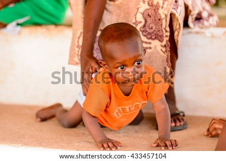 KARA, TOGO - MAR 9, 2013: Unidentified Togolese little baby boy in an orange shirt crowls and smiles. People in Togo suffer of poverty due to the unstable econimic situation
