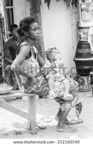 KARA, TOGO - MAR 9, 2013: Unidentified Togolese little girl with a wooden doll on her mother knees. Children in Togo suffer of poverty due to the unstable econimic situation