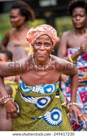 KARA, TOGO - MAR 9, 2013: Unidentified Togolese woman in a traditional African dress dances at the local music performance. People in Togo suffer of poverty due to the unstable econimic situation - stock photo