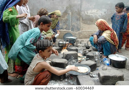 KARACHI, PAKISTAN - AUG 29: Flood affected children cook food at a flood relief camp on August 29, 2010 in Karachi.