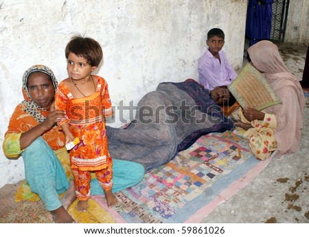 KARACHI, PAKISTAN, AUG 26: Flood affected women sit with their sick relative on floor at flood affectees relief camp established at a government school at Bhatiabad area on August 26, 2010 in Karachi, Pakistan
