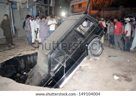 KARACHI, PAKISTAN - AUG 07: People gather after bomb blast during football match at  Bazinjo Road in Sango Lane of Lyari area on August 07, 2013 in Karachi.eleven people including five children died