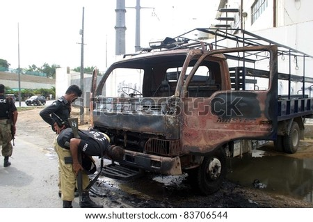 KARACHI, PAKISTAN - AUG 29: Policemen look burnt police van which was set ablaze by angry protesters during protest demonstration of employees of KESC on  August 29, 2011 in Karachi, Pakistan