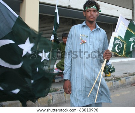 KARACHI, PAKISTAN - AUGUST 14: Two unidentified boys sell Pakistani
