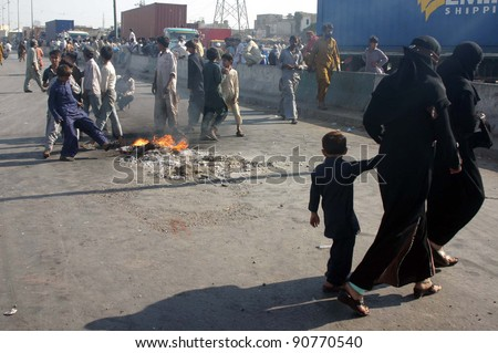 KARACHI, PAKISTAN - DEC 13: Angry protesters burn tires at Maripur road during protest demonstration of Kachi community against killing of their community members on December 13, 2011 in Karachi, Pakistan.