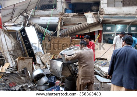 KARACHI, PAKISTAN - JAN 05: Rescuers are busy in work after roof collapse of a motel located nearby Habib Bank Plaza on January 05, 2016 in Karachi.