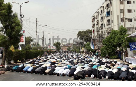 KARACHI, PAKISTAN - JUL 09: Shiite Muslims offering Zohrain prayer during procession on the occasion of Day of Martyrdom of Hazrat Ali (A.S), at M.A Jinnah Road on July 09, 2015 in Karachi.