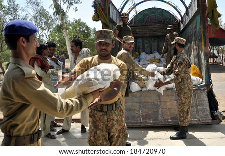 KARACHI, PAKISTAN - MAR 31: Pakistani Army soldier loads relief goods on a truck to be distributed to the famine-hit Tharparkar district, on March 31, 2014 in Karachi.