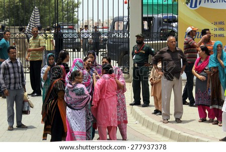 KARACHI, PAKISTAN - MAY 13: Ismaili people mourn the killing of their relatives as the  six unidentified assailants on motorbikes opened fire on a bus on May 13, 2015 in Karachi.  - stock photo