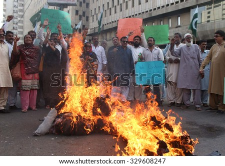 KARACHI, PAKISTAN - OCT 20: Activists of Muslim League-Q burning effigy of Indian PM  Modi as they are protesting against Hindu extremist party Shiv Sena on October 20, 2015 in Karachi.