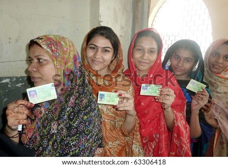 KARACHI, PAKISTAN - OCT 17: Women hold their National Identity Cards (NICs) to cast their votes at a polling station during by-election for PS-94 at Orangi Town on October 17, 2010 in Karachi.