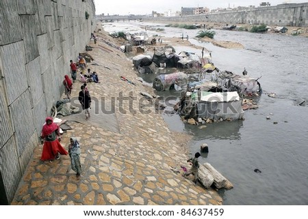 KARACHI, PAKISTAN - SEPTEMBER 13: A view of inundated make-shift hut houses which were established at Liyari Express Way due to heavy downpour of Monsoon Season in Karachi September 13, 2011.