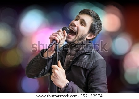 Karaoke concept. Young man holds microphone and singing a song on blurred background.