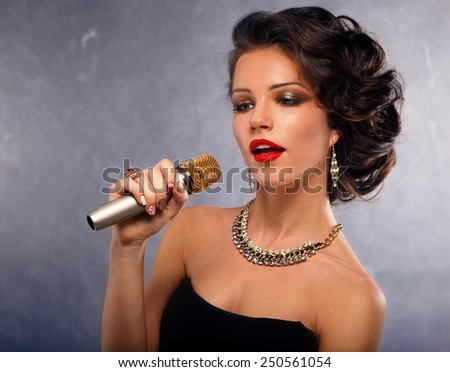Karaoke Song.Singing Woman with Microphone.Glamour Singer Girl Portrait. Vintage Style.  - stock photo