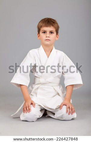 Karate boy in white kimono is sitting isolated on gray background
