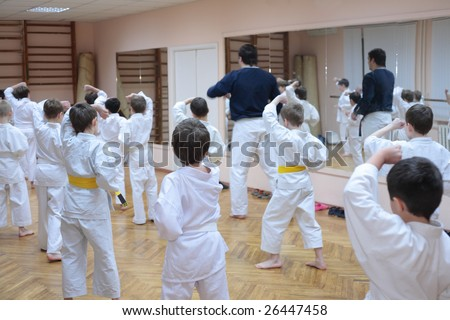karate boys training in sport hall, focus on left boy in yellow belt - stock photo
