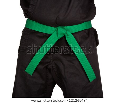 Karate green belt tied around marital artists torso wearing black dojo GI's.