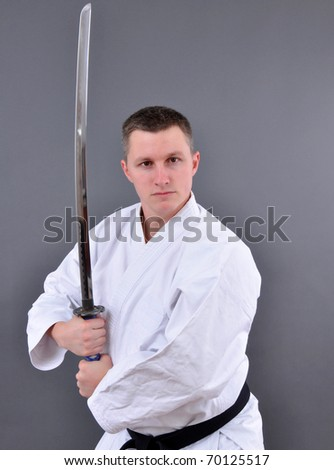 Karate man with single edged Japanese sword - stock photo