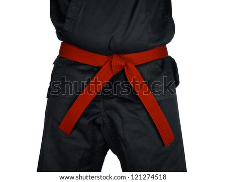 Karate red belt tied around marital artists torso wearing black dojo GI's.