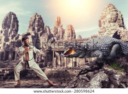 Karateka fights with crocodile - stock photo