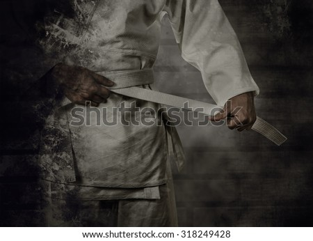 Karateka tying the white belt (obi) with grunge background - stock photo
