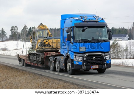 KARJAA, FINLAND -  MARCH 5, 2016: Blue Renault Trucks T hauls tracked excavator on lowboy trailer. Renault Trucks aims to grow their market share in Finland. - stock photo