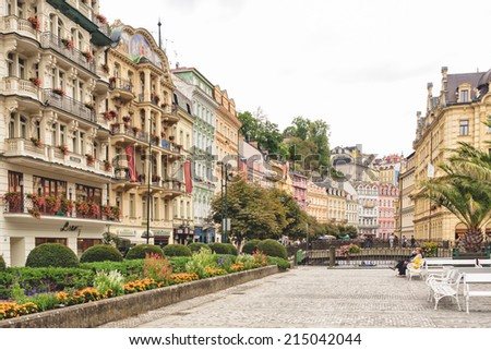KARLOVY VARY, CZECH REPUBLIC - SEPTEMBER 15 2012:  Tourists relax in pedestrian area in historical spa town famous for elaborate, pastel architecture, hot mineral springs, medical spa facilities. - stock photo