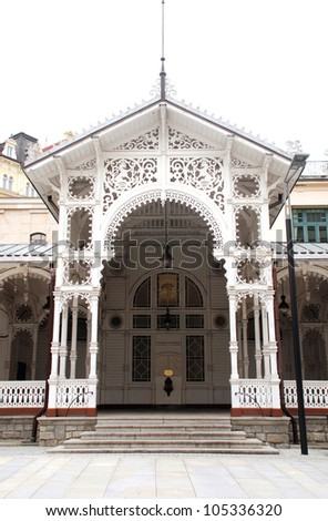 Karlovy Vary, Czech Republic. The Market Colonnade is decorated with various motifs of the lace, carved in wood. This white wooden building was built in 1883 near Charles IV Spring. - stock photo