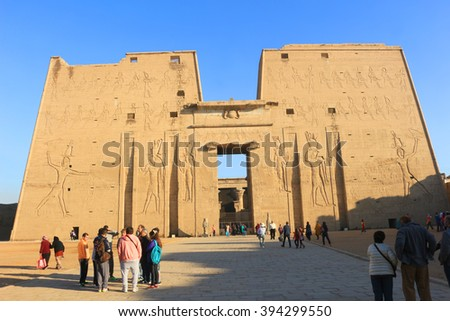KARNAK, EGYPT, FEBRUARY 3, 2016: Entrance with people and  carvings of gods and  heiroglyphs written on the walls  in Ancient Egypt at Karnak Temple  - stock photo
