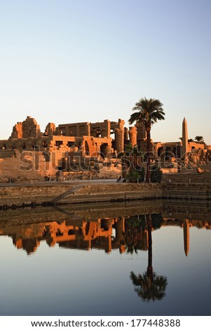 Karnak Temple and the Sacred Lake at sunrise. Karnak was the residence of gods, Amon-Re, his wife Mut, and their son Khonsu, the moon god. Built in the 12th dynasty, 2000 B. C. - 220 B. C.
