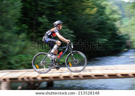KAROLINKA, CZECH REPUBLIC - AUGUST 08, 2014: Female racer rides the Valachia Man triathlon - stock photo