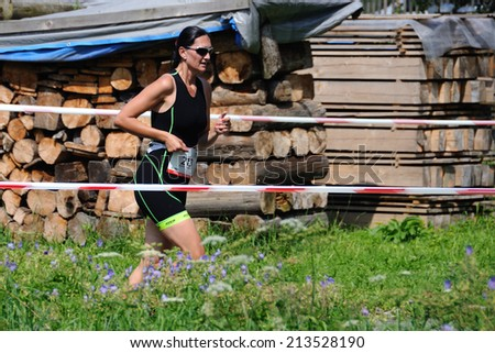 KAROLINKA, CZECH REPUBLIC - AUGUST 08, 2014: Female racer runs the Valachia Man triathlon - stock photo
