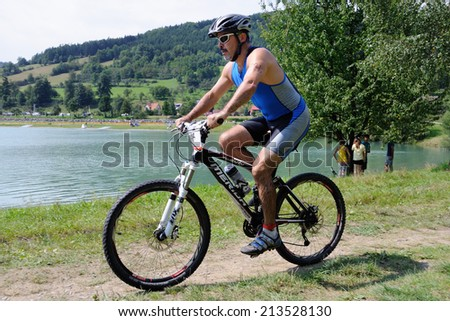 KAROLINKA, CZECH REPUBLIC - AUGUST 08, 2014: Male racer rides the Valachia Man triathlon - stock photo