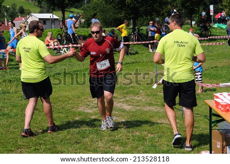 KAROLINKA, CZECH REPUBLIC - AUGUST 08, 2014: Male racer takes refrehement at the Valachia Man triathlon - stock photo
