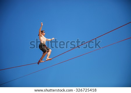 KAROLINO-BUGAZ, UKRAINE - AUGUST 24. Highline walker participating in competition at Z-Games extreme sports festival on August 24, 2015 in Karolino-Bugaz, Ukraine. - stock photo