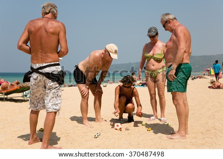 KARON BEACH, THAILAND - CIRCA FEBRUARY, 2015: European tourists are playing the French game boules (petanque). Karon beach is one of the most popular beaches among tourists in Phuket - stock photo