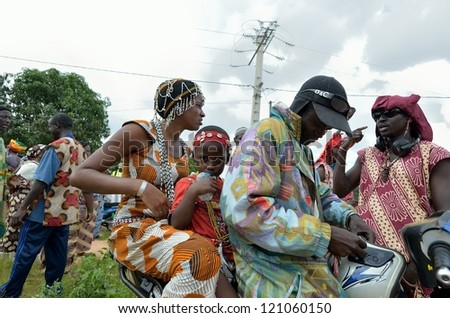 KARTIAK,SENEGAL-SEPT 18:family in motorbike,go to the ritual of Boukoutt of Initiation ceremony on Sept 18,2012 in Kartiak,Senegal.The ceremony occurs every 30 years and celebrates boys becoming men