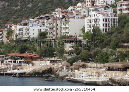 KAS, TURKEY - OCTOBER 15, 2009: Modern Apartment buildings and beach with Cliffs in the village Kas in Turkey. Kas is a small fishing, diving, yachting and tourist town and part of Antalya Province.  - stock photo