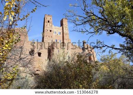 Kasbah Tamdaght with trees against blue sky. - stock photo