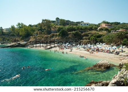 Kassiopi Beach, Corfu Island, Greece. Sunbeds and parasols (sun umbrella) on the beach. Tourists relaxing on beautiful beach of Kassiopi in the north area of Corfu Island. - stock photo