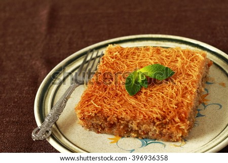 Kataif cake on a plate with fresh mint.